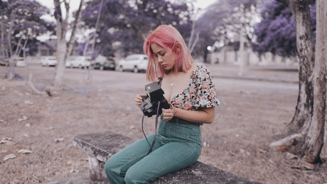 Urban trendy woman holding an old photo camera