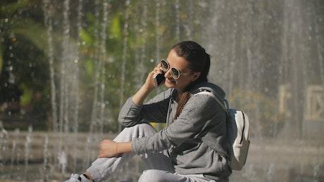 Urban woman taking a call next to a fountain
