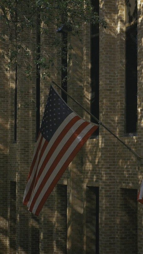 USA and Texas flags waving at a state building