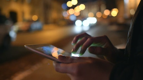 Using a tablet on the street by night