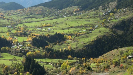 Valley with a town surounded by mountains in autumn