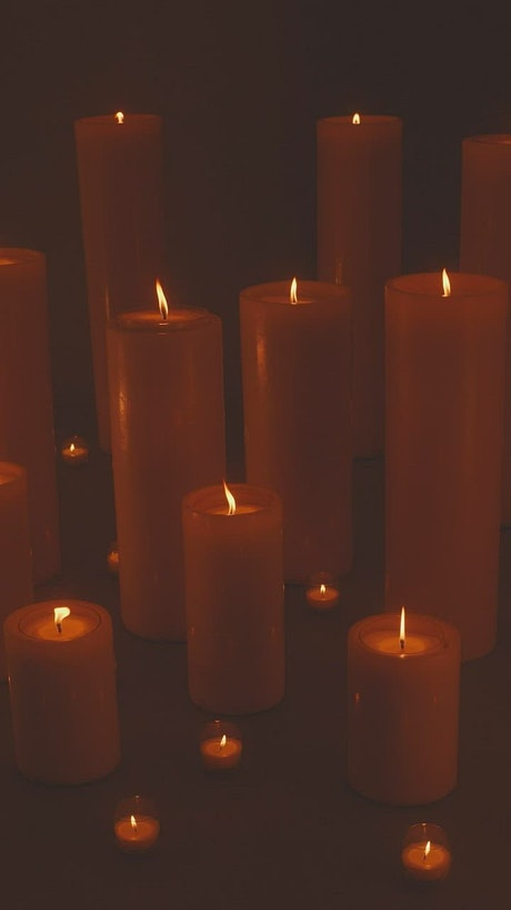 Very large and very small candles lit in the dark