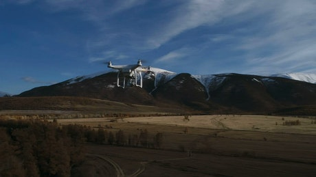 View of drone flying over trees towards mountain