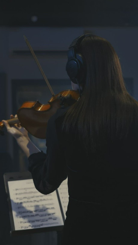 Violinist playing a sheet music in a recording studio