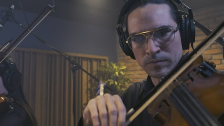 Violinist trio playing in a studio booth