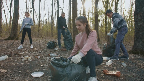 Volunteers collect garbage from the forest