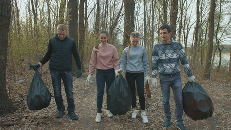 Volunteers with garbage bags in the forest
