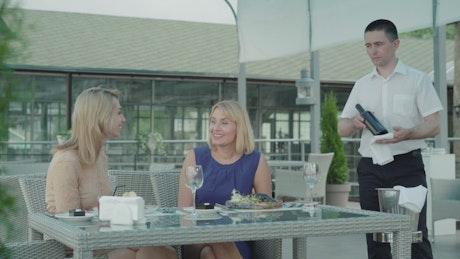 Waiter presents wine to women dining in outdoor restaurant