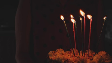 Walking in the dark with cake with candles