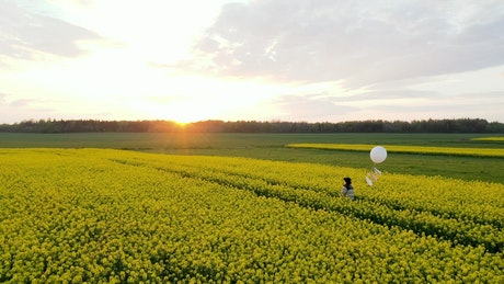 Walking on a flower field with a white balloon