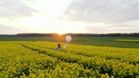 Walking on a flower field with a white balloon at sunset