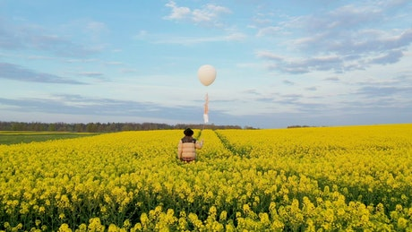 Walking on a flower field with a white balloon in hand