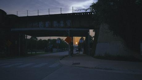 Walking through the city under a bridge at sunset