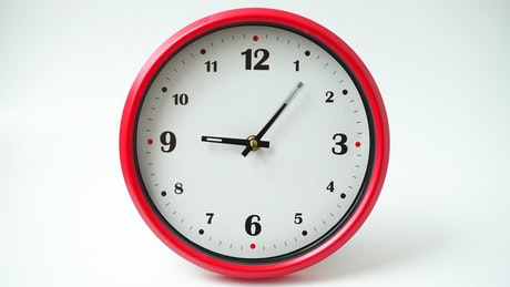 Wall clock on white background, time-lapse