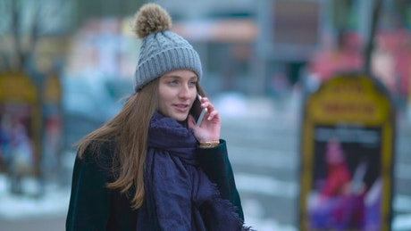 Warm girl walking while talking on the phone