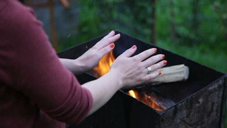 Warming her hands over a fire