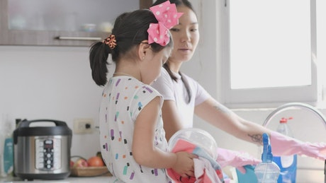 Washing the dishes together, Mom and daughter