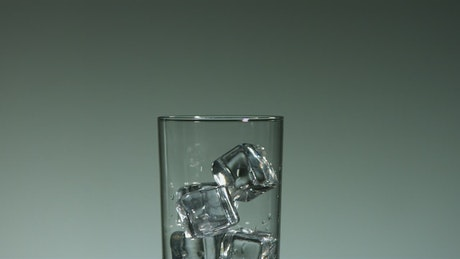 Water drops falling into a glass with ice cubes