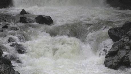 Water flowing down the river between black rocks
