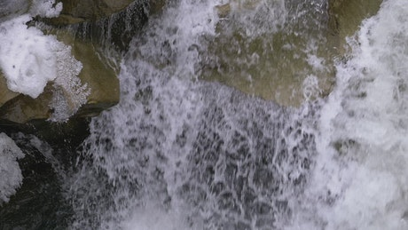 Water flowing through the rocks in the winter