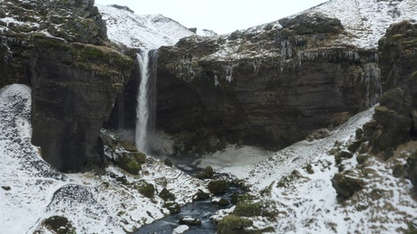 Waterfall at the end of a river during in winter