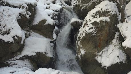 Waterfall between snowy rocks