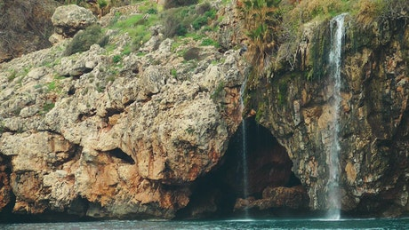 Waterfall on a rocky shoreline by the sea