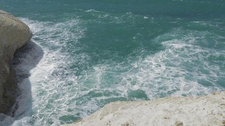 Waves against chalk cliffs