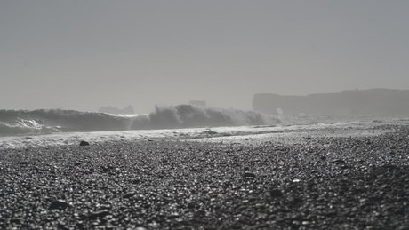 Waves breaking over black sand