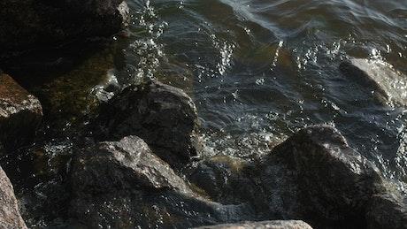 Waves breaking over harbor rocks