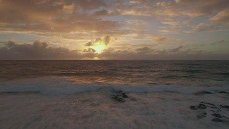 Waves breaking over rocks at dusk
