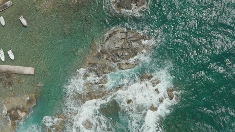 Waves breaking the rocky seashore of a tourist port