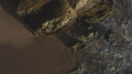 Waves crash on a cliff