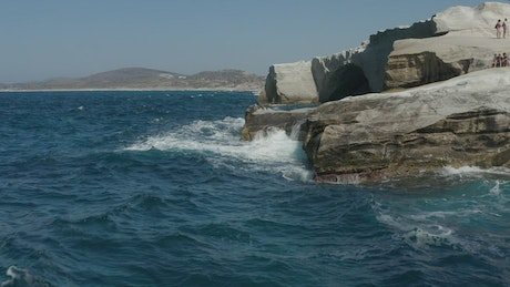 Waves hitting a rocky cliff in Greece