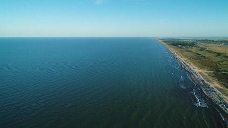 Waves of a long blue sea reaching the beach