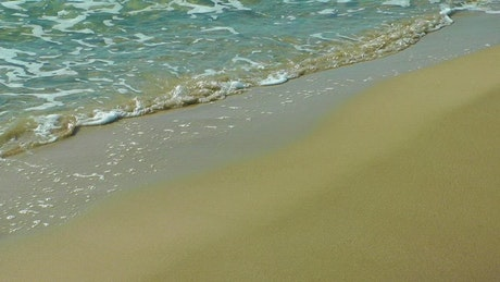 Waves on a beach, viewed in a close take