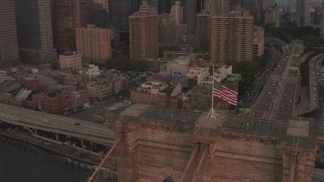 Waving USA flag at the top of the Brooklyn Bridge