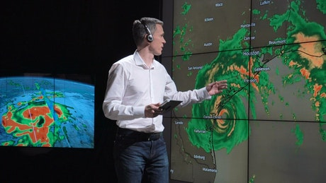 Weatherman showing a hurricane on the screen