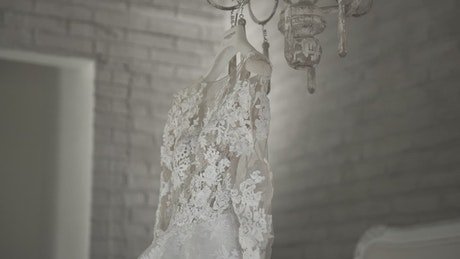 Wedding dress hanging on a chandelier