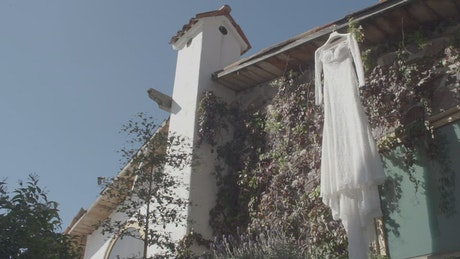 Wedding dress hanging outside a house