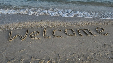 """Welcome"" in the sand at the seashore"