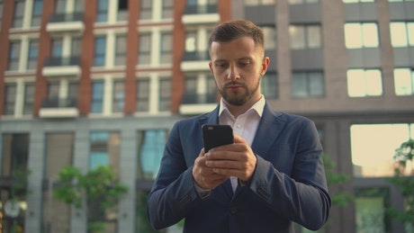 Well dressed businessman sending messages on his cell phone