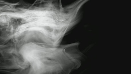 White smoke floating in front of a black background
