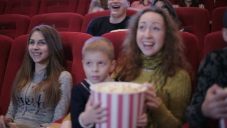 Whole family watching a funny movie at the cinema