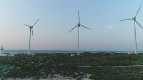 Wind turbines next to a lighthouse
