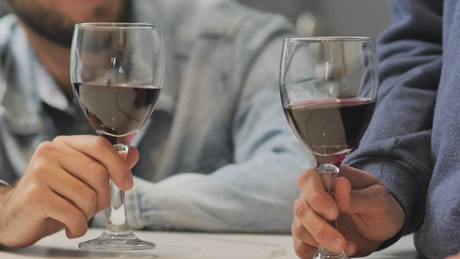 Wine glasses toast during a LGBTQ men's date