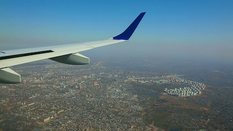 Wing view of an airplane flying above the city