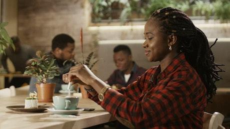 Woman adding sugar to her coffee