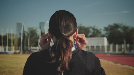 Woman adjusting her headphones to start running