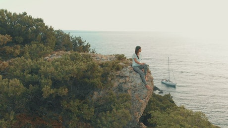 Woman admiring the sea from a cliff